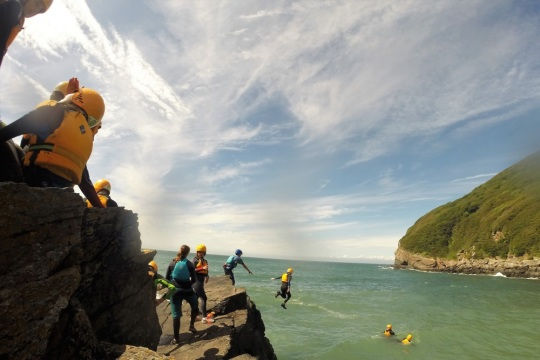 Group jumping into sea from cliffs by Channel Adventure